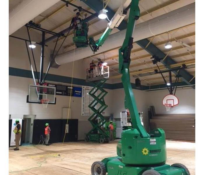SERVPRO inside the gym of the school fixing a water leak