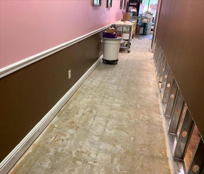 Hallway in local business with removed drywall and floorboards