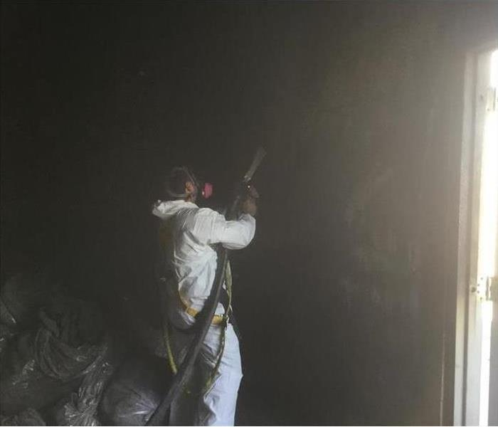 Restoration technician cleaning air area of a building damaged by smoke