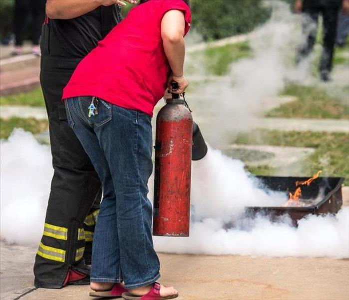 Somebody being trained to use a fire extinguisher properly